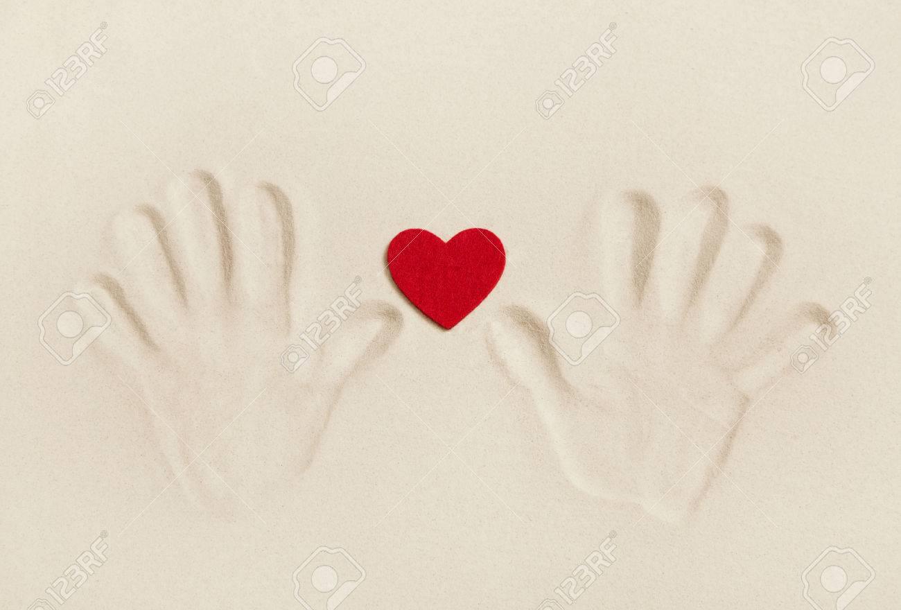 Duas Mãos Imprimir Na Areia Com Um Coração Vermelho  Conceito